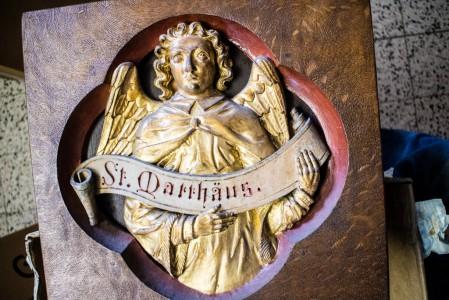 Symbol des Evangilisten Matthäus am oberen Kreuzbalken. Stammt aus dem alten Hochaltar und wird sicher auch dort wieder seinen Platz finden